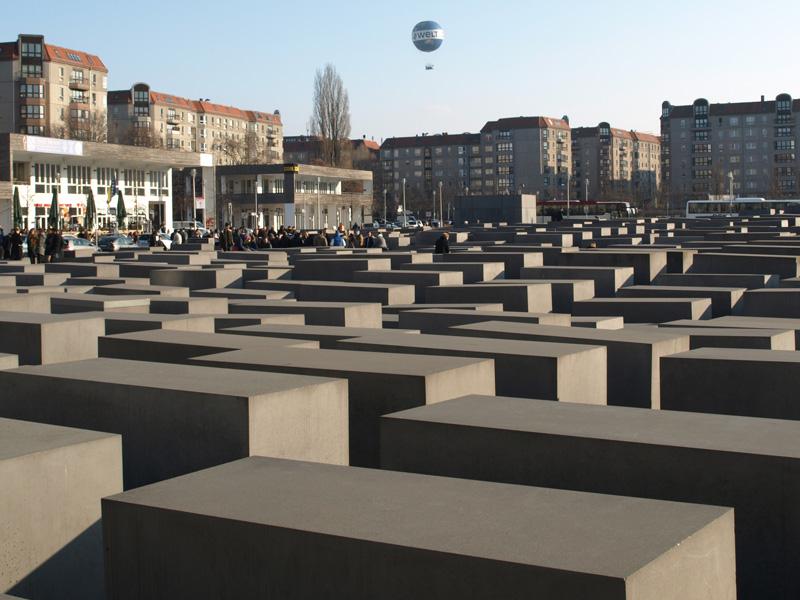 Stelenfeld des Denkmals für die Ermordeten Juden Europas vor Fassaden der DDR-Plattenbauten