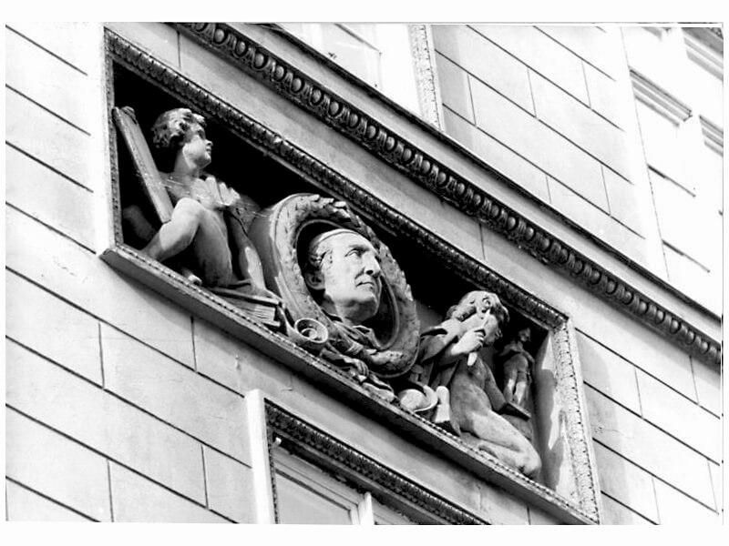 Die Büste des Künstlers – von einem seiner Schüler modelliert – schaut von oben aus einen Rundrelief auf die Straße herab.